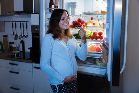 pregnant women donuts: Young Pregnant Woman Eating Donut In Front Of Refrigerator In Kitchen Stock Photo
