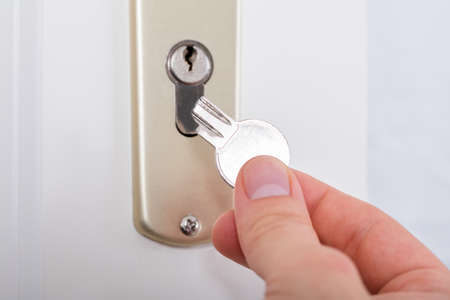 Close-up Of Persons Hand Holding Broken Key Inserting In Keyhole