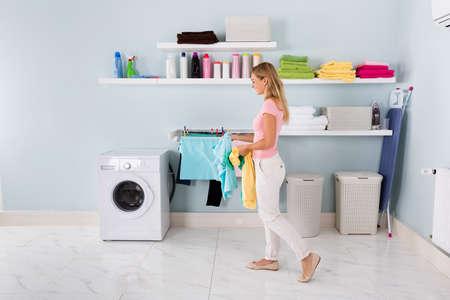 Glückliche Frau Waschen Stained Kleidung in der Waschmaschine Im Hauswirtschaftsraum Standard-Bild - 69397220