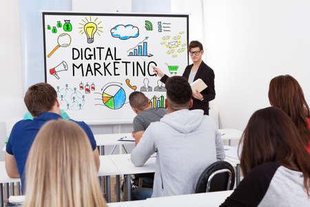 teacher teaching: Male Teacher Teaching Digital Marketing To Students In Classroom Stock Photo