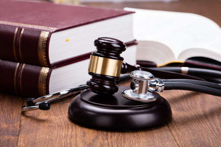 autoridad: Marrón mazo con el médico estetoscopio cerca de libro en el escritorio de madera en la sala de tribunal