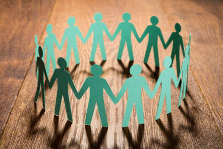 Cut Out Of Paper Representing People Holding Hands Together On Wooden Desk Stock Photo