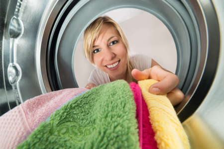 inserting: Close-up Of Young Smiling Woman Inserting Clothes In Washing Machine Stock Photo