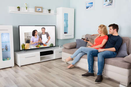 Young Couple Watching Cooking Show On Television At Home