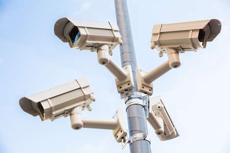 Low Angle View Of Four Security Camera Installed On Pole Stock Photo