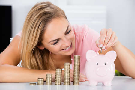 inserting: Young Happy Woman Inserting Coin In The Piggybank Near Stack Of Coins On Desk Stock Photo