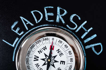 Close-up Of Compass With Leadership Text On Blackboard Stock Photo