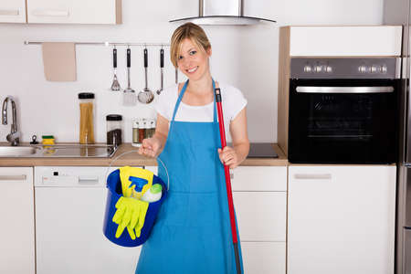 housemaid: Cleaning Service Professional Housemaid Holding Gloves And Equipment In Kitchen At Home