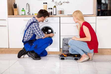 defects: Woman Looking At Male Worker Checking The Defects In Washing Machine