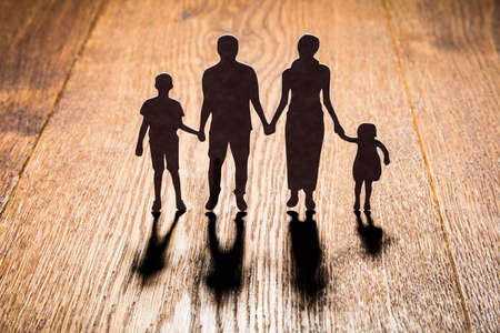 Silhouette Of Family Papercut On Wooden Desk