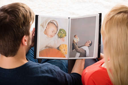 High Angle View Of Young Couple Looking At Photo Album photo