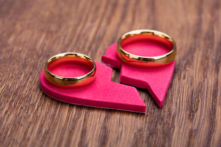 High Angle View Of Golden Ring On Red Broken Heart At Wooden Desk Banque d'images