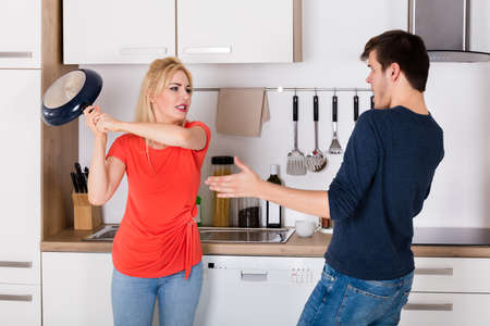 Wife Hitting With Husband Pan During Divorce Argument In Kitchen At Home