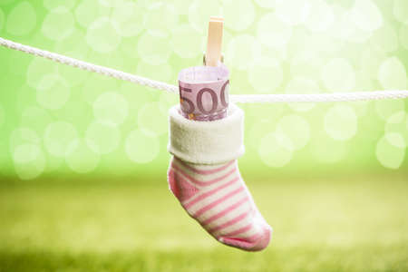 care allowance: Baby Sock With Dollar Hanging On Rope Using Wooden Clip