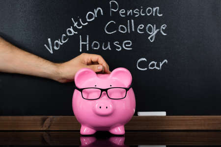 piggy: Person Hand Inserting Coin In Piggybank For Daily Expenses In Front Of Blackboard