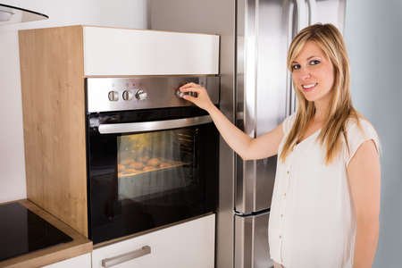 Smiling Young Woman Using Oven For Baking Cookies In Kitchen
