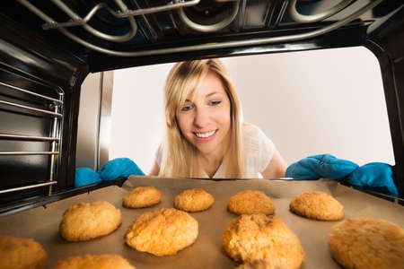 inserting: Smiling Young Woman Inserting Cookies Tray In Oven At Kitchen Stock Photo