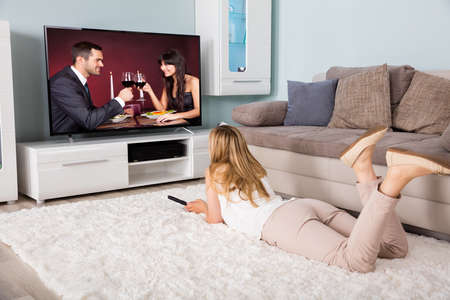 Young Woman Lying On Carpet Watching Movie On Television At Home photo
