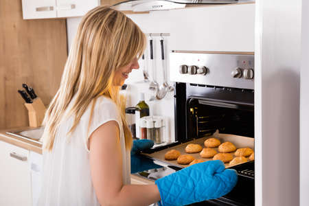 cookie sheet: Close-up Of Young Woman Placing Tray Full Of Cookies In Oven At Kitchen