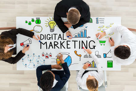 high angle view: High Angle View Of Businesspeople Drawing Digital Marketing Diagram On Office Desk With Colorful Marker