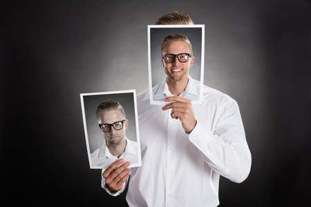 sadness: Sad Man Holding Smiling Picture In Front Of His Face Against Black Background
