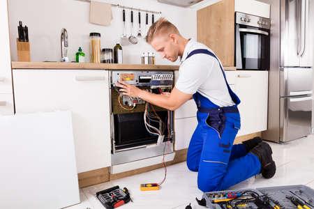 Young Repairman Checking Dishwasher With Digital Multimeter Stock fotó