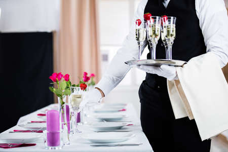 serve: Waiter Serving Champagne On Banquet Table At Restaurant Stock Photo