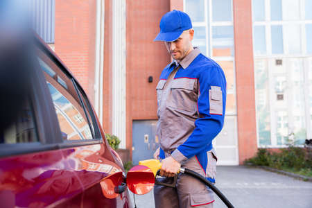 bomba de gasolina: Man Refueling Cars Tank By Holding Petrol Pump Nozzle