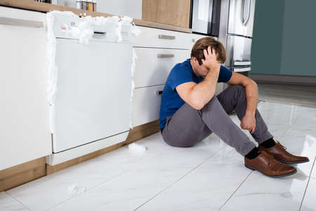 Upset Young Man Sitting Next To Dishwasher With Foam Coming Out In Kitchen