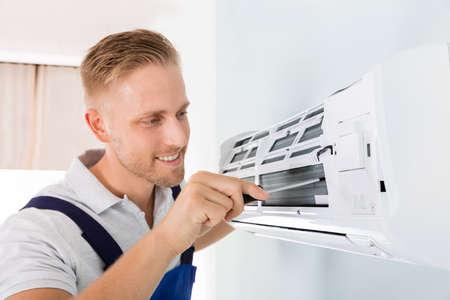 Happy Male Technician Repairing Air Conditioner With Screwdriver Stockfoto