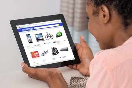 Close-up der afrikanischen Frau Doing Online Shopping On Digital Tablet zu Hause Standard-Bild