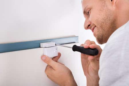 sensor: Close-up Of Technician Installing Security System Door Sensor Using Screwdriver Stock Photo