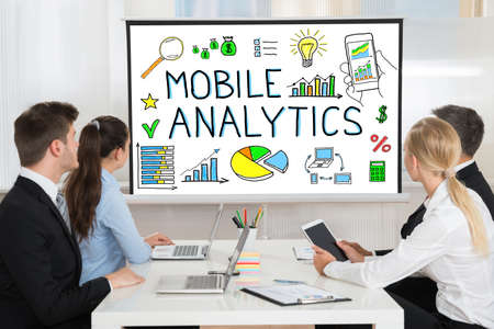 marketing strategy: Businesspeople Looking At Mobile Analytic Concept On Projector Screen In Conference Room