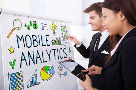 quantitative: Two Happy Businesspeople Discussing Mobile Analytics On Flipchart Using Digital Tablet In Office Stock Photo