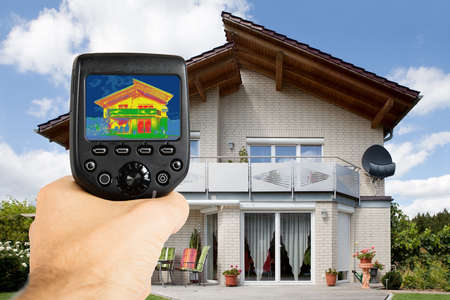 thermal image: Close-up Of Person Hand Recording Heat Loss With Infrared Thermal Camera Outside The House