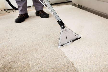 Close-up d'un tapis Nettoyage Personne Avec Aspirateur