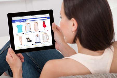 확대 여자의 집에서 디지털 태블릿에서 온라인 쇼핑을하는