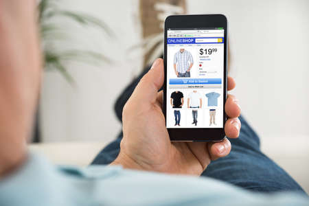 スマート フォンでオンライン ショッピングをしながら布を買っている男性をクローズ アップ