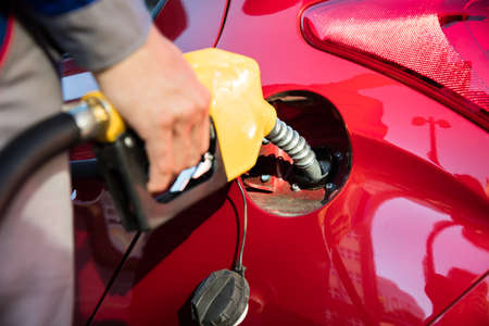 Persons Hand Refueling Cars Tank By Holding Petrol Pump Nozzle Stock Photo