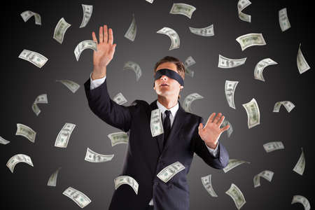 sightless: A Blindfolded Lost Businessman Standing Under Money Rain On Gray Background Stock Photo