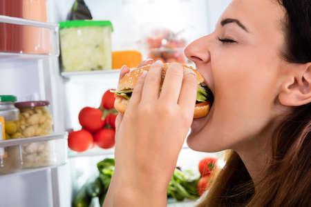 woman eating: Young Woman Eating Delicious Hamburger Near Open Fridge