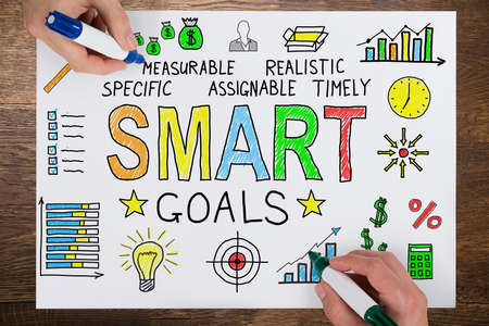 smart goals: Two People Using Colorful Marker For Drawing Smart Goals Concept On White Paper Stock Photo