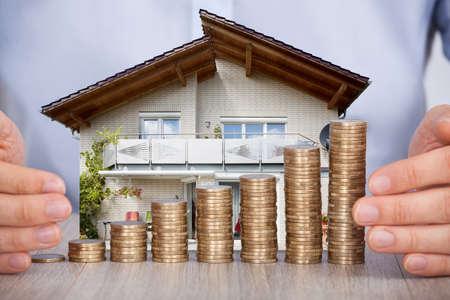 家モデルおよび木製の机の上のコインのスタックを保護する人間の手のクローズ アップ