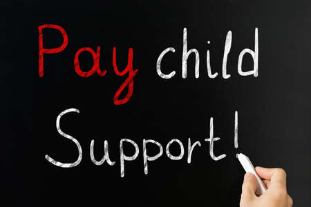 person writing: Person Hand Writing Pay Child Support With Exclamatory Sign On Blackboard With Chalk Stock Photo