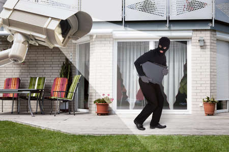 camera: Security Camera Capturing Thief Wearing Balaclava Running With Laptop Outside The House Stock Photo