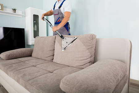 Young Male Worker Cleaning Sofa With Vacuum Cleaner Photo
