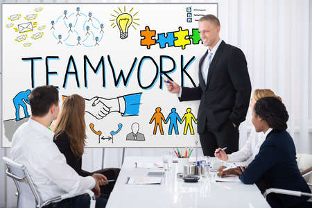 office presentation: Businessman Giving Presentation Regarding Teamwork To His Colleagues In Office Stock Photo