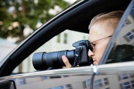Paparazzi assis à l'intérieur de la photographie de voiture avec caméra SLR Banque d'images - 69611585