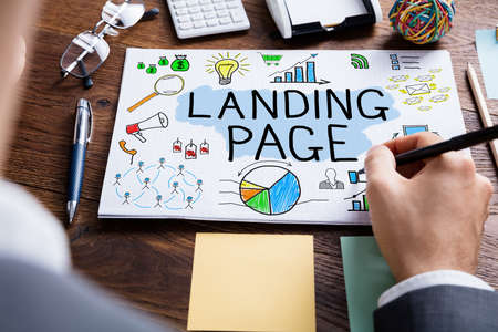 high angle view: High Angle View Of Businessperson Drawing Landing Page Concept At Wooden Desk Stock Photo