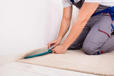 Primer plano de una alfombra de ajuste de artesano en el piso con cortador
